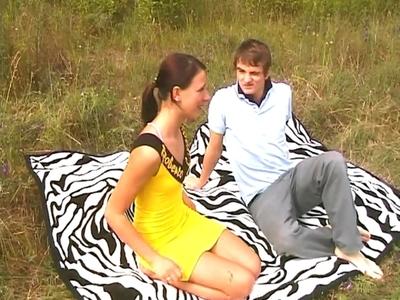 Un couple de jeunes gens se prélasse sur le gazon d'une maison de campagne. Piqu